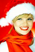 foto of santa-claus  - portrait of beautiful blond young woman wearing santa claus hat on red background - JPG