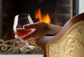 Resting at the burning fireplace fire with a glass of cognac