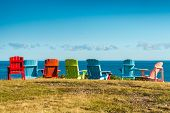 Постер, плакат: 7 empty colourful chairs facing the sea