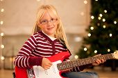 Girl with guitar in front of Christmas tree