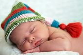 image of newborn baby girl  - Sleeping baby girl wearing a striped hat - JPG