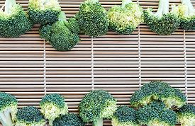 picture of cruciferous  - row of fresh broccoli on pattern bamboo for background - JPG