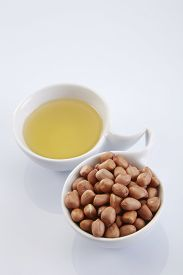 stock photo of ground nut  - bowl of oil and ground nut - JPG