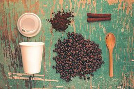 foto of coffee grounds  - Coffee Drink Break Top View Vintage Toned Concept with Roasted Coffee Beans Ground Spoon Plastic Cup and Cinnamon Sticks on Rustic Wood Background - JPG
