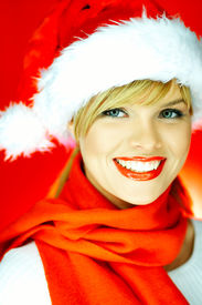 stock photo of santa claus hat  - portrait of beautiful blond young woman wearing santa claus hat on red background - JPG