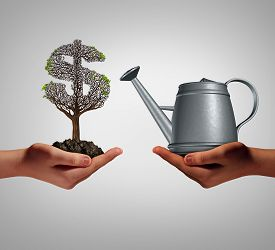 stock photo of struggle  - Financial assistance and business help concept as two hands holding a watering can and a struggling money tree as a budget aid relief symbol for investing in growth support service and helping a struggling economy - JPG