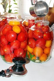 image of boiling water  - red tasty tomatos in jars which are been flooding by boiling water prepared for preservation - JPG