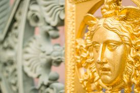 picture of medusa  - A golden painted metal face of the Sun or Medusa on an iron fence with copy space for text  - JPG