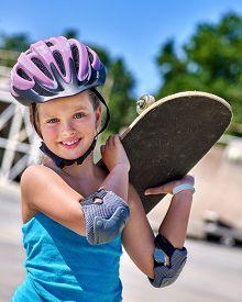 stock photo of skateboard  - Kid skateboarding his skateboard and hold on her back outdoor - JPG