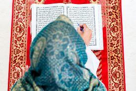 picture of muslim  - Asian Muslim woman reading Koran or Quran on praying carpet wearing traditional dress - JPG