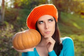stock photo of beret  - Pensive girl with crocheted orange beret and pumpkin - JPG