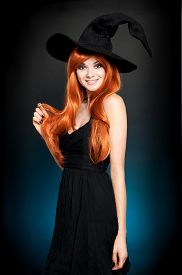 image of scroll  - Beautiful young woman as halloween witch with scroll - JPG