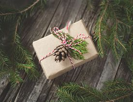 picture of cone  - Hand crafted gift on rustic wooden background with with fir branches and cones  - JPG