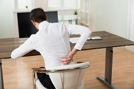 foto of suffering  - Young Businessman Sitting On Chair And Suffering From Backache At Desk - JPG