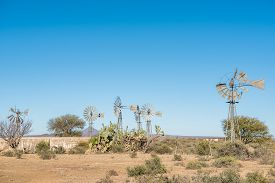 foto of windmills  - Many windmills and a concrete dam on a farm between Britstown and Vosburg in the Northern Cape Karoo Region in South Africa - JPG