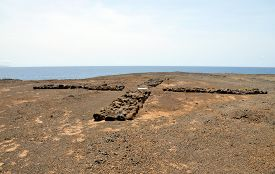 picture of mural  - Large cross mural created from stones formed by visitors to the uninhabited islet of Djeu in Cabo Verde - JPG