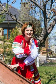 picture of early 50s  - Fiftieth woman in Russian national dress on the background of the house in the early spring - JPG