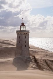 stock photo of sandstorms  - Sandstorm at the lighthouse Rubjerg Knude in North Jutland Denmark - JPG