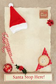 stock photo of letters to santa claus  - Christmas letter to santa claus with stop here sign on parchment with holly and decorations over old brown paper background.  - JPG