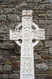 foto of celtic  - Celtic cross gravestone against ancient stone wall background - JPG