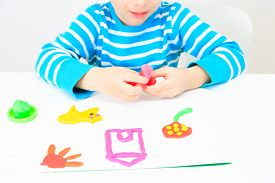 image of daycare  - little boy playing with clay dough - JPG