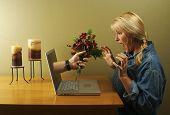 Hand & Blumen kommen durch Laptop-Bildschirm