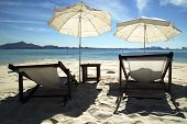 stock photo of dynamo  - Tropical beachfront with a couple of chairs and umbrella - JPG