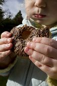 Child Snacking On Unhealthy Chocolate Donut