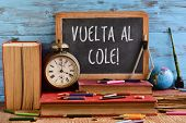 wooden-framed chalkboard with the text vuelta al cole, back to school in spanish written in it on a  poster