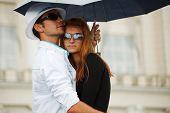 Casal jovem com guarda-chuva na chuva