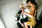 Young couple fighting on a party in the toilette, he is obviously drunk