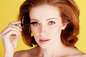 Beauty shot of a pretty redhead woman applying mascara to her eyelashes