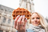 Young Beautiful Tourist Woman Holds Out A Traditional Belgian Waffle To The Camera On The Background poster