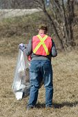 stock photo of pick up  - A man wearing a reflective vest picking up garbage in his town - JPG