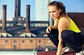 picture of parkour  - Young woman traceur balances on the edge of the roof of an industrial building while assessing the challenges of her immediate environment for parkour - JPG