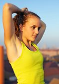 stock photo of parkour  - Closeup portrait of a beautiful young female traceur standing on an urban rooftop stretching in readiness for demonstrating parkour - JPG