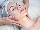 Beautician Doing Facial Massage By Hands In Beauty Parlour. Female Face In Disposable Cap With Close poster