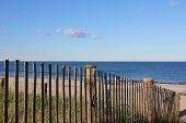 New England Beach Past A Fence