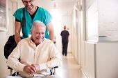 Male Orderly Pushing Senior Male Patient Being Discharged From Hospital In Wheelchair poster