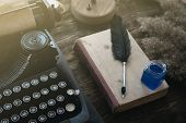 Typewriter, Old Book And A Quill Pen With A Inkwell On An Author Desk Table Background. poster