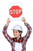 Female builder holding stop sign