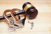 Judges Gavel Or Law Mallet, Handcuffs And Key On Light Wooden Background With Copy Space. Judgement, poster