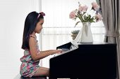 Side View Of Young Little Asian Cute Girl Playing Electronic Piano At Home. Seen From Side View Whil poster