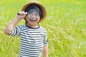 Young Boy Exploring Nature In The Meadow With A Magnifying Glass Looking At Flowers. Curious Childre poster