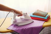 The Woman The Housewife Irons Clothes At Home. On The Ironing Board Iron And Purple T-shirt, As Well poster