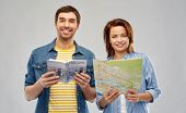 travel, tourism and vacation concept - happy couple of tourists with city guide and map over grey ba poster