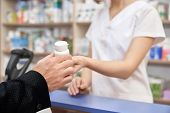 Pharmacist Working With Customers In Pharmacy At Counter. Woman Giving To Client Medicaments. Man Bu poster