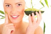 picture of face mask  - A portrait of a young woman applying natural avocado mask on her face - JPG