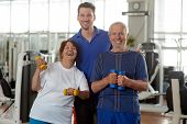 Happy Senior People With Personal Fitness Trainer. Portrait Of Joyful Elderly Couple With Personal I poster