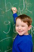 Young boy writing on chalk board